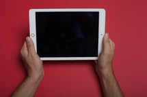 Hands holding an electronic tablet on a red background.