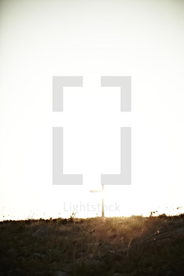 Sun shining on a cross in a field