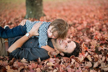 father and son hugging in fall leaves