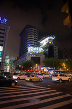 a car crossing through a crosswalk in a city at night