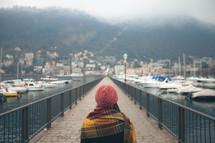 a woman bundled up standing on a dock near a marina