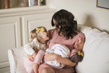 mother holding a swaddled newborn baby and toddler daughter in a chair