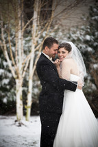 bride and groom hugging under falling snow
