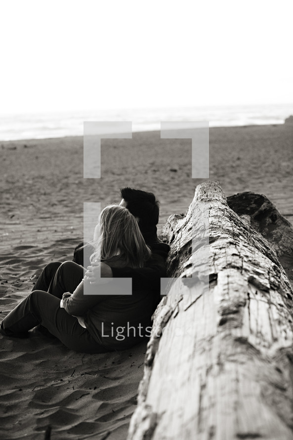 Happy couple sitting on beach sand tree marriage relationship love