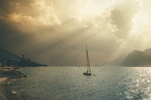 rays of sunlight shining through clouds onto a sailboat