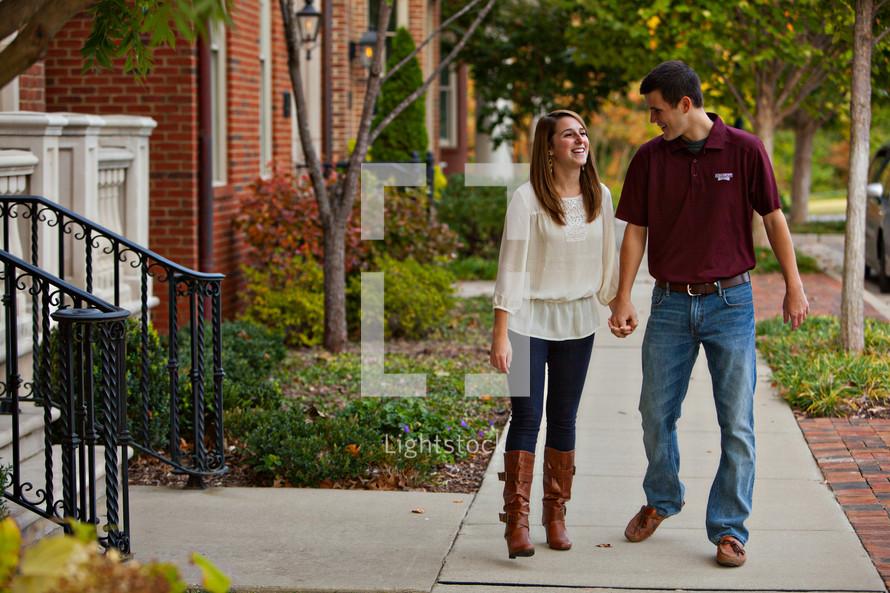 Happy couple walking on sidewalk