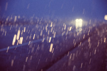 headlights from cars and falling rain