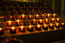 Rows of lit votive candles.