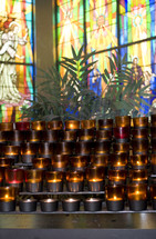 prayer candles in front of stain glass windows
