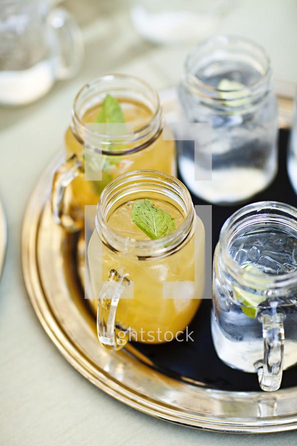 Drinks sitting on a tray lemonade and ice water mason jars
