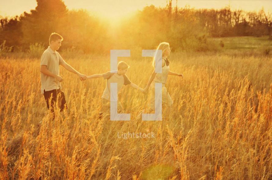 siblings holding hands walking in a field