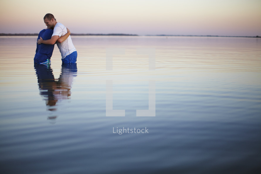Men hugging after baptism
