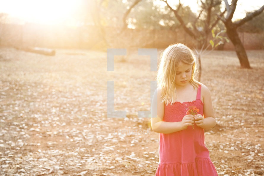 girl holding a flower outdoors