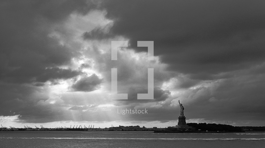 sun shining through the clouds over the Statue of Liberty
