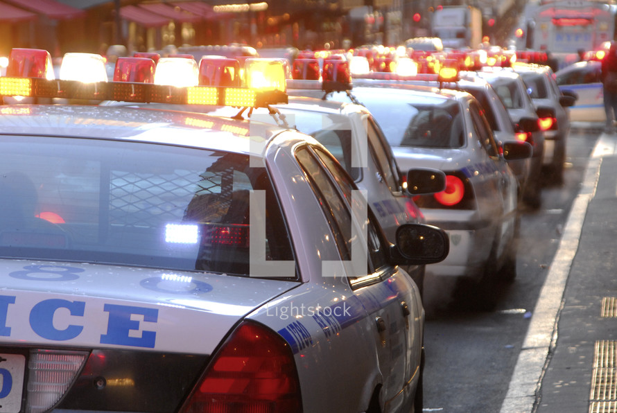 Line of police cars with lights flashing at an officers funeral in New York City.