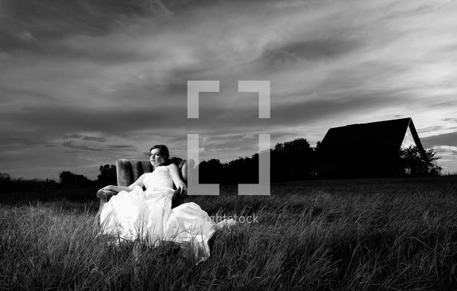 bride sitting in a chair in a field