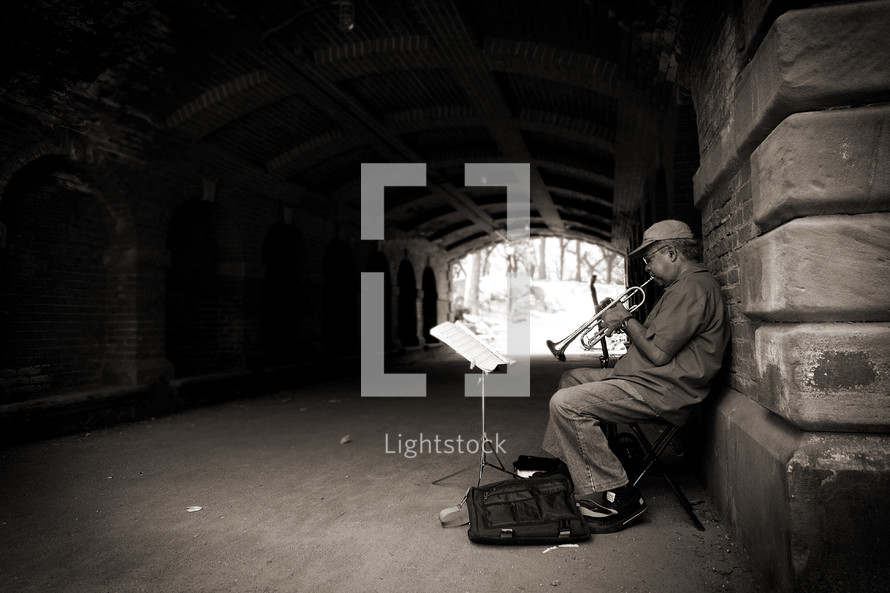 street musician playing a trumpet under a tunnel