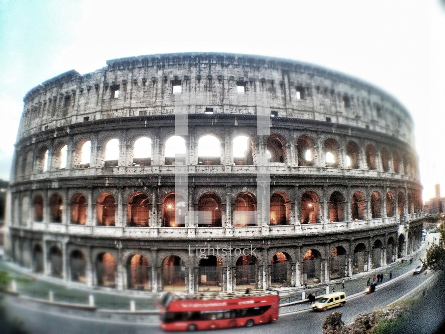 The Colosseum during the day surrounded by red bus and cars in traffic.