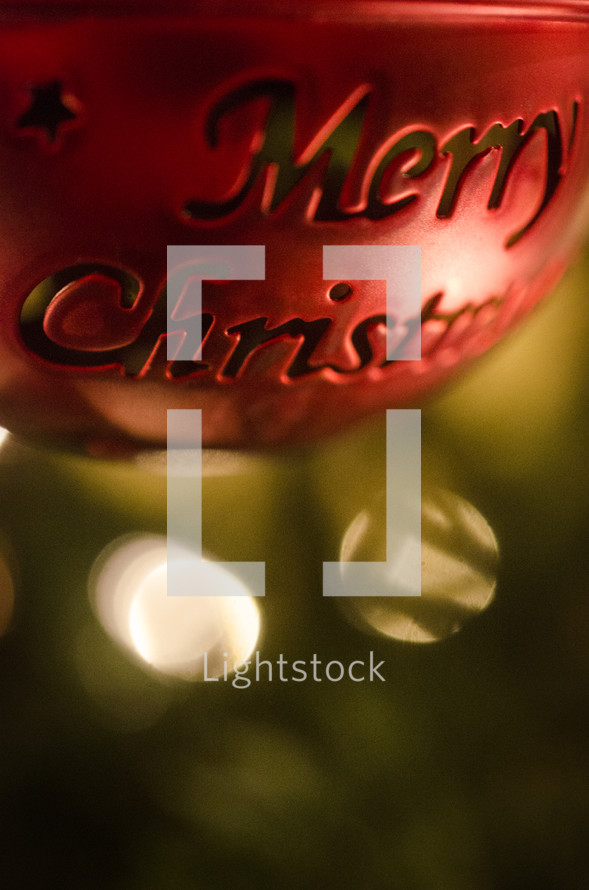 Close up of red metal ball ornament with Merry Christmas hanging from Christmas tree.