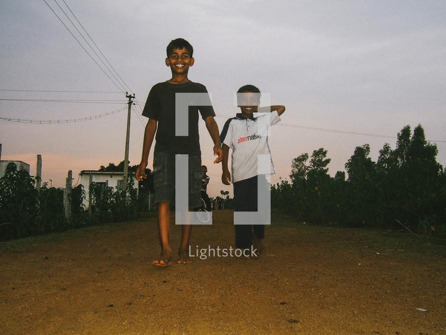 boys walking barefoot down a dirt road at night