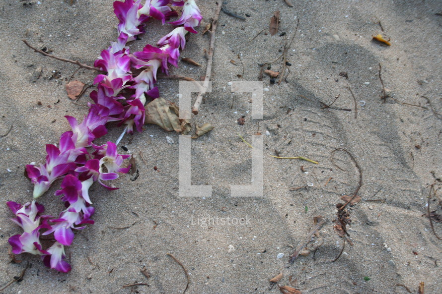 Footprints in the sand near hawaiian lei