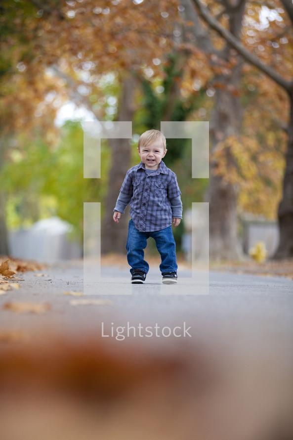 Toddler standing on sidewalk smiling