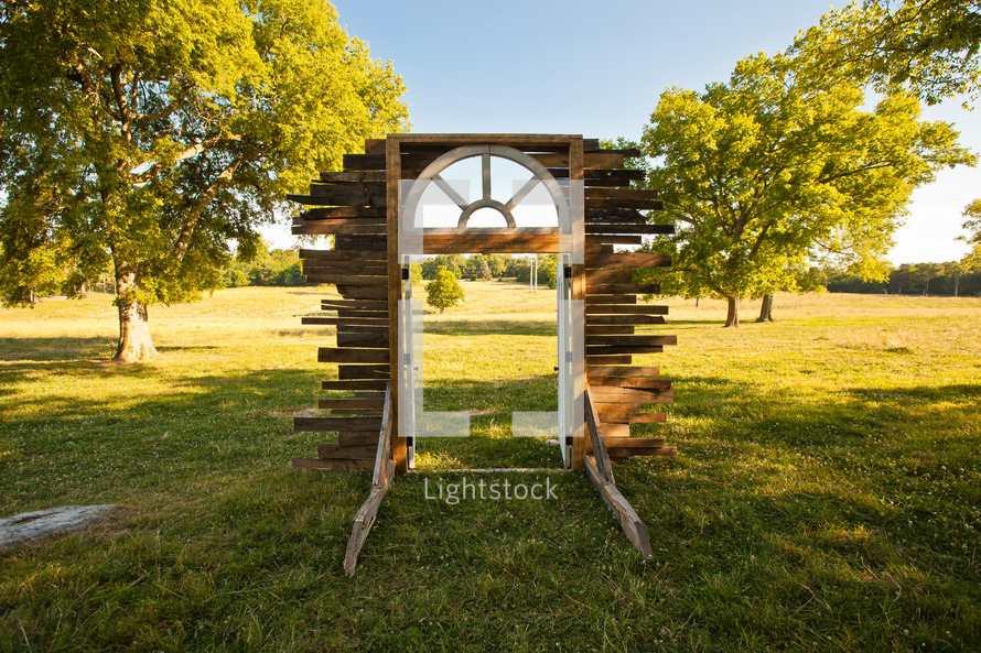 Window frame erected in the middle of a grassy green field with trees.