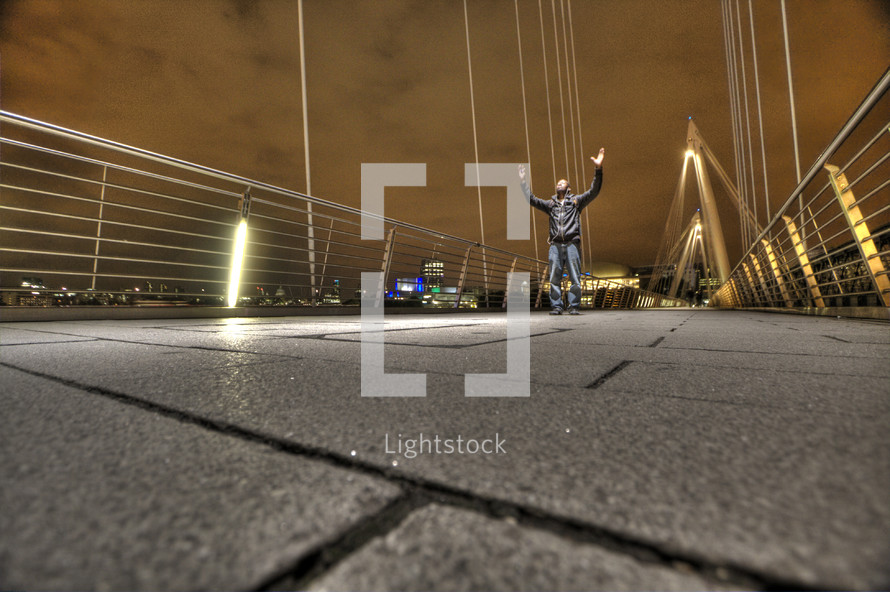 Man on bridge with hands raised