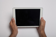 Hands holding an electronic tablet on a white background.