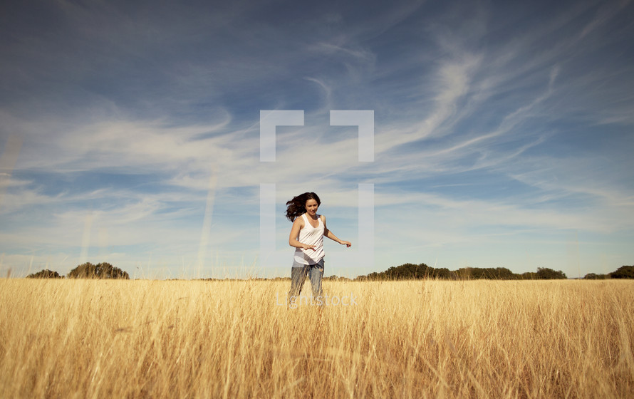 A woman running through a field with the sky overhead