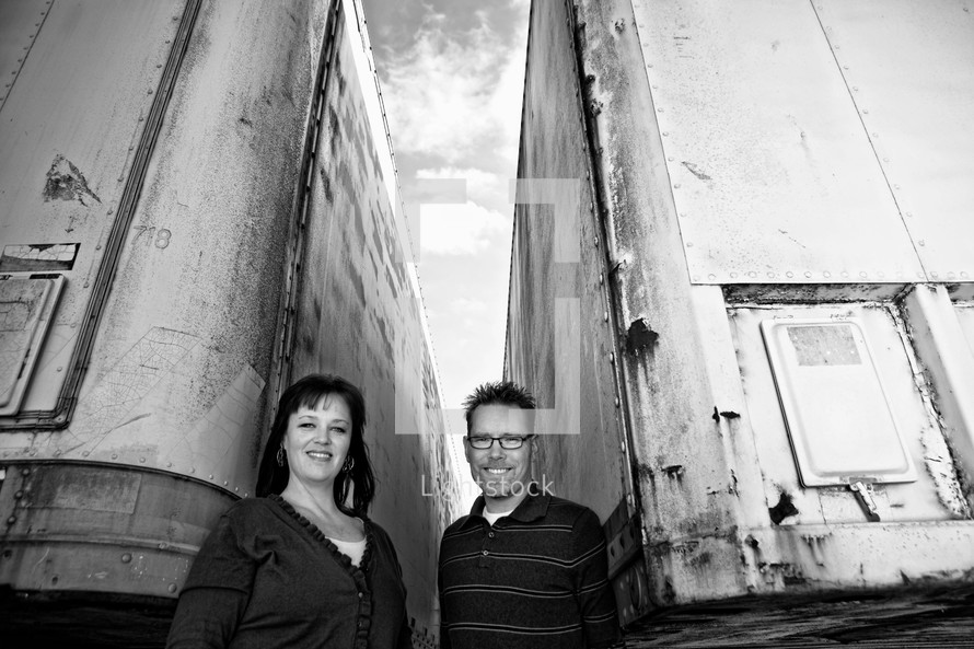 man and a woman standing between two tractor trailers