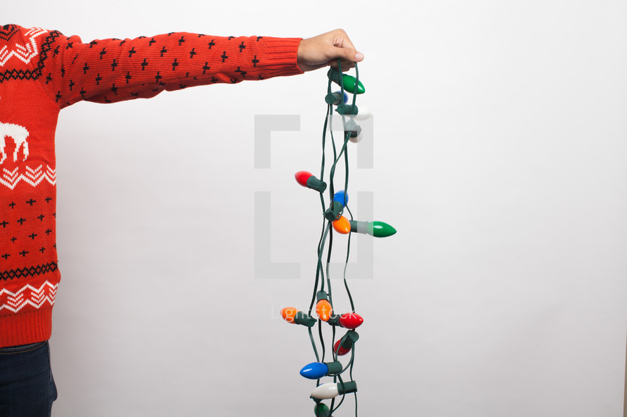 arm holding a string of Christmas lights