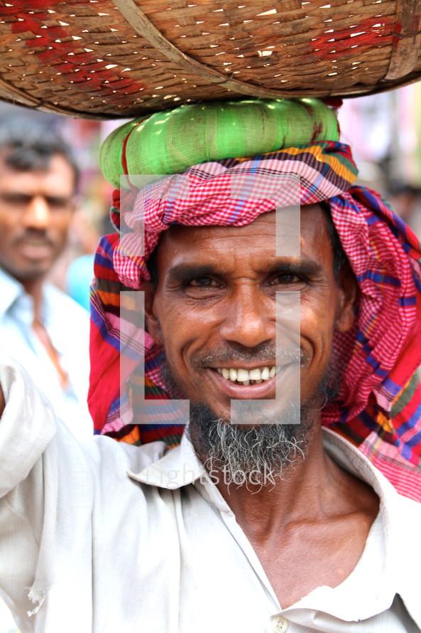 Bangladeshi man with a basket on his head