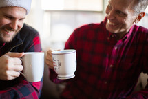 Men smiling and drinking coffee at a Christmas party