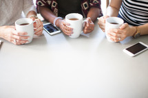 Three people sitting at a table with cell phones and coffee cups.