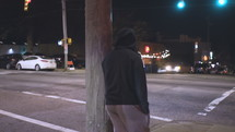 a young man leaning against a pole on a city sidewalk at night