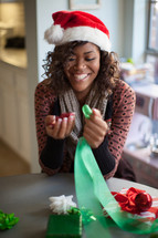 A smiling woman in a santa hat decorating for Christmas