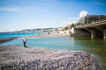 a fisherman on a rocky beach in Nice, France