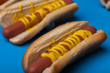 Hot dogs and buns drizzled with mustard on a blue background.