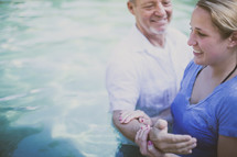 Man baptizing a woman in a pool of water.
