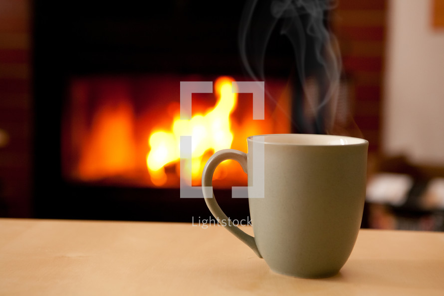 Steaming coffee cup and fireplace