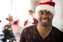 A man in a santa hat smiling at a Christmas party