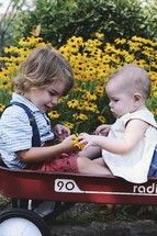 a brother and sister playing with flowers while sitting in a red wagon