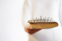 a woman holding a tiara and a Bible