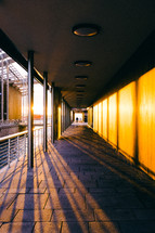 rays of sunlight shining onto pavers in a long covered walkway