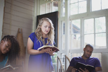 woman reading a Bible to a group at a Bible study