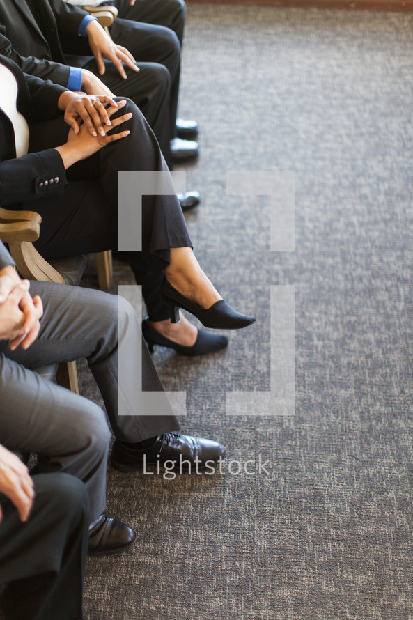 legs of businessmen and businesswomen sitting in chairs in meeting