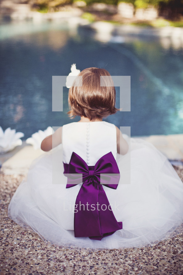 flower girl sitting by a pool