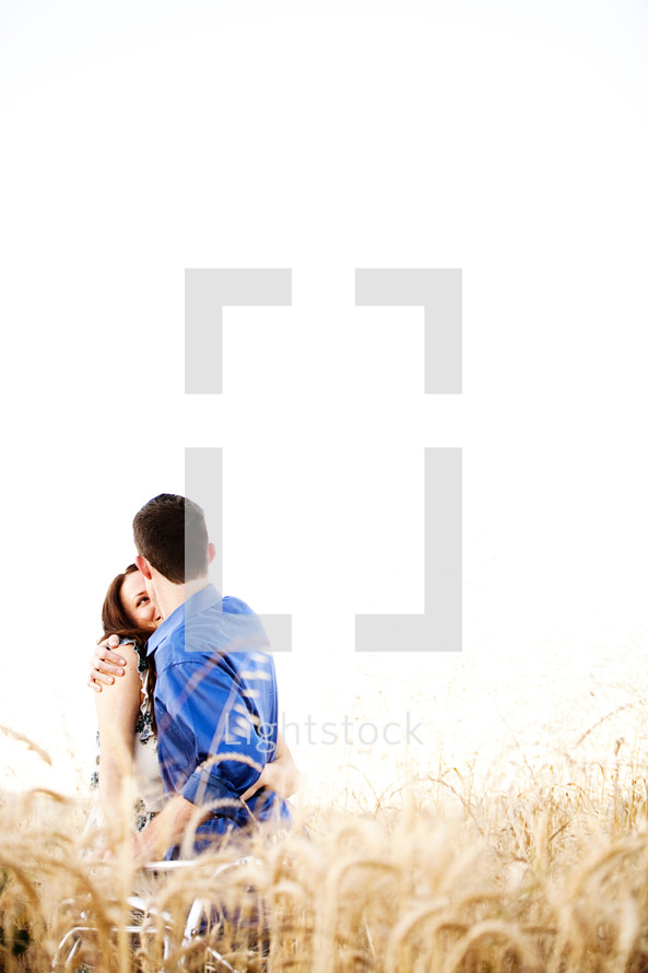 Happy couple embracing in wheat field