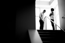 man and woman standing at the top of stairs talking